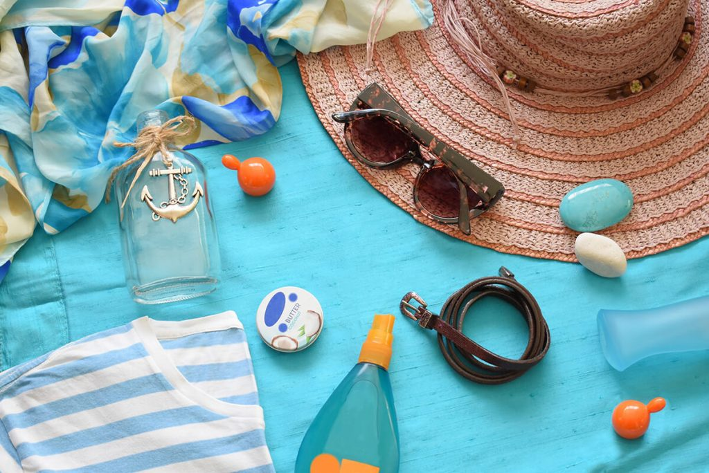 Summer on the beach with sunglasses, sunscreen, and bottle, on a towel