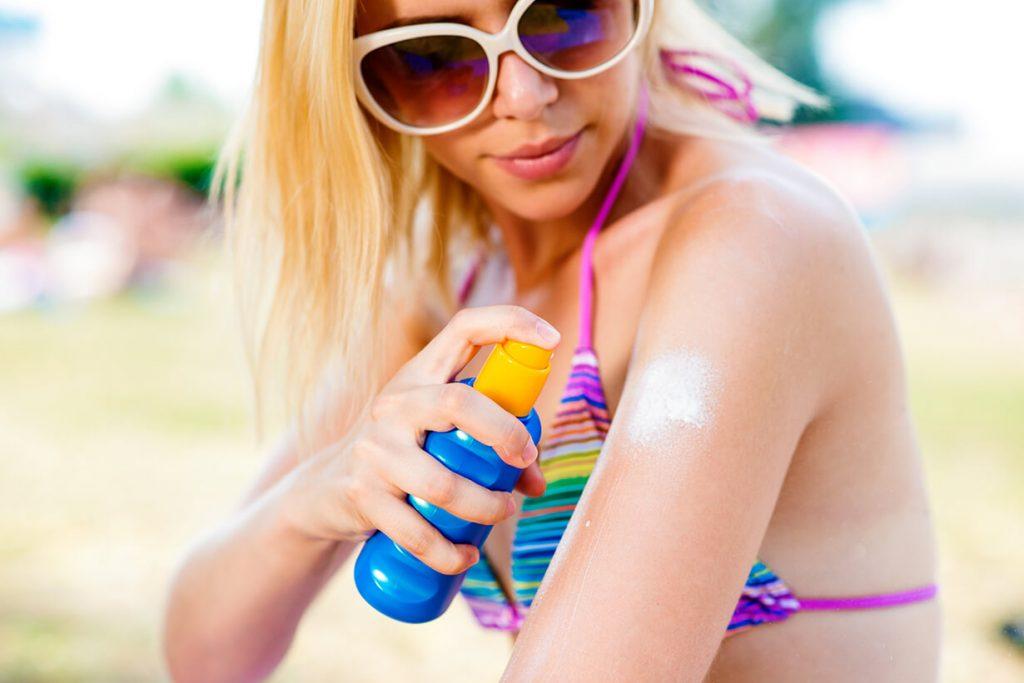 Woman in bikini spraying on sunscreen
